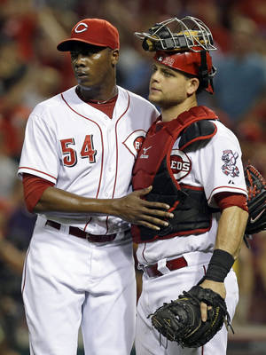 Photo - Cincinnati Reds relief pitcher Aroldis Chapman (54) congratulates catcher Devin Mesoraco after they defeated the Oakland Athletics 3-1 in a baseball game, Tuesday, Aug. 6, 2013, in Cincinnati. (AP Photo/Al Behrman)
