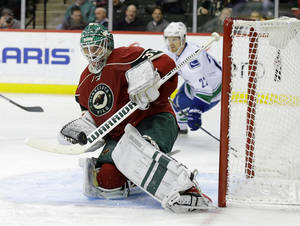 Photo - Minnesota Wild goalie Josh Harding (37) deflects a shot by the Vancouver Canucks during the second period of an NHL hockey game in St. Paul, Minn., Tuesday, Dec. 17, 2013. (AP Photo/Ann Heisenfelt)
