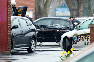 Photo - In this photo taken April 21, 2014, a body bag is rolled into a coroner's van at the scene of a fatal shooting in the parking lot at St. Mary's School in Griffith, Ind. Nina Castro, 42, was shot to death by her estranged husband, Remanard Castro, 55, who later died of a self-inflicted gunshot wound at his home after a police officer confronted him, police said. (AP Photo/The Times, Kyle Telechan) MANDATORY CREDIT; CHICAGO LOCALS OUT;  GARY OUT.