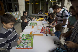 Photo - Collecters exchange World Cup stickers for their albums at a trading table outside the Pacaembu stadium in Sao Paulo, Brazil, Saturday, May 10, 2014. The frenzy over the World Cup sticker album has taken over Brazil like never before. Brazilians have long been avid fans of World Cup albums, but this year there's added motivation with the soccer tournament coming to their backyard. (AP Photo/Andre Penner)