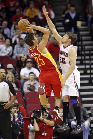 Photo - Houston Rockets forward Chandler Parsons (25) is challenged by Atlanta Hawks guard Kyle Korver (26) on a shot during the first half of an NBA basketball game, Monday, Dec. 31, 2012, in Houston. (AP Photo/Bob Levey)