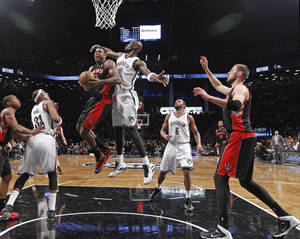 Photo - Brooklyn Nets forward Kevin Garnett (2) defends Toronto Raptors forward Amir Johnson (15) as teammates watch from the floor in the first half of an NBA basketball game, Monday, Jan. 27, 2014, in New York. (AP Photo/Kathy Willens)