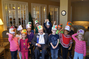 Photo - Above: Elementary school students from Heritage Hall pose with Fountains at Canterbury resident Sam Moore on his 100th birthday. The students visited Moore to mark the 100th day of classes on Tuesday.
