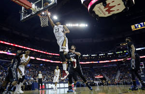 Photo - New Orleans Pelicans power forward Anthony Davis (23) goes to the basket in front of Minnesota Timberwolves power forward Kevin Love (42) in the first half of an NBA basketball game in New Orleans, Friday, Feb. 7, 2014. (AP Photo/Gerald Herbert)
