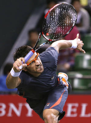 Photo -   Janko Tipsarevic of Serbia returns to Gilles Simon of France during their first round match of the Japan Open tennis championships in Tokyo Wednesday, Oct. 3, 2012. (AP Photo/Shuji Kajiyama)