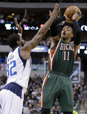 Photo - Dallas Mavericks' O.J. Mayo (32) defends as Milwaukee Bucks' Monta Ellis (11) shoots during the first half of an NBA basketball game Tuesday, Feb. 26, 2013, in Dallas. (AP Photo/Tony Gutierrez)
