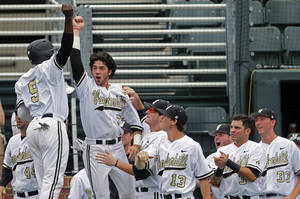 Photo - Vanderbilt's Dansby Swanson (7) and Xavier Turner (9) celebrate with teammates after scoring during the first inning of an NCAA college baseball Super Regional tournament game against Stanford Friday, June 6, 2014, in Nashville, Tenn. (AP Photo/Wade Payne)
