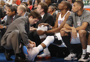 Photo - Trainers attend to the ankle of Oklahoma City Thunder small forward Kevin Durant (35) during the NBA basketball game between the Oklahoma City Thunder and the Los Angeles Clippers at Chesapeake Energy Arena on Wednesday, March 21, 2012 in Oklahoma City, Okla.  Photo by Chris Landsberger, The Oklahoman