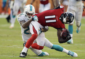 Photo - Miami Dolphins cornerback Nolan Carroll (28) tackles Atlanta Falcons wide receiver Julio Jones (11) during the second half of an NFL football game, Sunday, Sept. 22, 2013, in Miami Gardens, Fla. The Dolphins defeated the Falcons 27-13.  (AP Photo/Lynne Sladky)