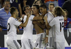 Photo - Real Madrid's Cristiano Ronaldo from Portugal, center, is congratulated by teammates after scoring a goal against Levante,  during their La Liga soccer match at the Ciutat de Valecia stadium in Valencia, Spain, Saturday, Oct. 5, 2013. (AP Photo/Alberto Saiz)