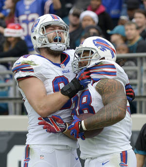 Photo - Buffalo Bills tight end Scott Chandler (84) celebrates with fullback Frank Summers, right, after Summers caught a 1-yard touchdown pass against the Jacksonville Jaguars during the second half of an NFL football game in Jacksonville, Fla., Sunday, Dec. 15, 2013.(AP Photo/Phelan M. Ebenhack)