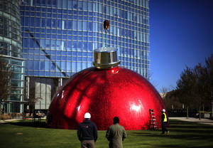 Photo - Workers install a large Christmas decoration in front of the Devon Towerr, Tuesday, November 13, 2012 in Oklahoma City. Photo by Sarah Phipps, The Oklahoman