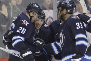 Photo - Winnipeg Jets' Blake Wheeler (26), Bryan Little (18) Dustin Byfuglien (33) and Andrew Ladd (16) celebrate Little's goal against the Phoenix Coyotes during second-period NHL hockey game action in Winnipeg, Manitoba, Thursday, Feb. 27, 2014. (AP Photo/The Canadian Press, John Woods)