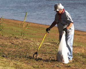 photo - Don Wiard picks up trash during the annual Arcadia Lake sweep. He was among 60 volunteers helping.