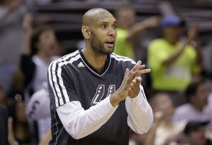 Photo - San Antonio Spurs' Tim Duncan cheers his teammates during the second half in Game 1 of a Western Conference Finals NBA basketball playoff series against the Memphis Grizzlies, Sunday, May 19, 2013, in San Antonio. San Antonio won 105-83. (AP Photo/Eric Gay)