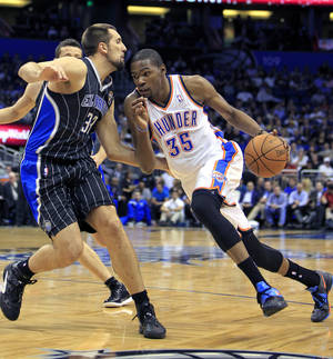 Photo - Oklahoma City's Kevin Durant, right, drives around Orlando's Ryan Anderson during the first half of Thursday's game. AP PHOTO