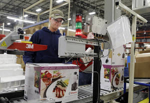Photo - In this April 15, 2014 photo, completed blenders roll off the packaging line at the Vitamix manufacturing facility in Strongsville, Ohio. The Commerce Department reports on wholesale trade inventories for March on Friday, May 9, 2014. (AP Photo/Mark Duncan)