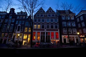 Photo - In this photo taken Tuesday, Feb. 4, 2014, the entrance of the 'Red Light Secrets' prostitution museum is seen, center, in Amsterdam. On any given evening, thousands of tourists stroll down the narrow streets of Amsterdam's famed Red Light District, gawking at ladies in lingerie who work behind windows, making a living selling sex for money. Now a small educational museum is opening in heart of the district that aims to show reality from the other side of the glass. Organizer Melcher de Wind says the Red Light Secrets museum is for those who want to learn more about how the area works without actually visiting a prostitute. (AP Photo/Evert Elzinga)