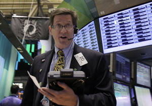 Photo -   Trader Christopher Forbes works on the floor of the New York Stock Exchange Wednesday, Oct. 24, 2012. Stocks are opening higher on Wall Street, following a big drop the day before, after big companies including Boeing reported stronger profits. (AP Photo/Richard Drew)