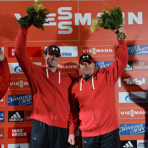Photo - Winner Steven Holcomb, left,  and Steven Langton of the U.S. celebrate on the podium after  the two-men bob race at the Bob World  Cup  in Innsbruck, Austria, on Saturday, Jan. 18. 2014. (AP Photo/Kerstin Joensson)