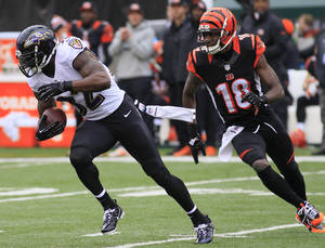 Photo - Baltimore Ravens strong safety James Ihedigbo (32) runs away from Cincinnati Bengals wide receiver A.J. Green (18) after intercepting a pass in the first half of an NFL football game on Sunday, Dec. 29, 2013, in Cincinnati. (AP Photo/Tom Uhlman)