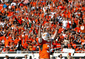 Photo - OSU's Brandon Weeden celebrates a touchdown during the college football game between the Oklahoma State University Cowboys (OSU) and the Baylor University Bears at Boone Pickens Stadium in Stillwater, Okla., Saturday, Nov. 6, 2010. Photo by Sarah Phipps, The Oklahoman