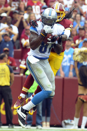 Photo - Detroit Lions wide receiver Calvin Johnson pulls in a touchdown pass under pressure from Washington Redskins strong safety Brandon Meriweather during the second half of a NFL football game in Landover, Md., Sunday, Sept. 22, 2013. (AP Photo/Richard Lipski)