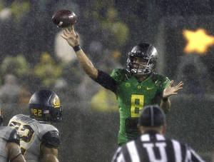Photo - Oregon quarterback Marcus Mariota unleashes a pass during the first half of an NCAA college football game against California in Eugene, Ore., Saturday, Sept. 28, 2013. (AP Photo/Don Ryan)