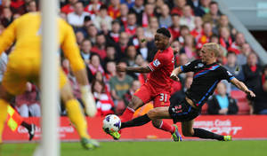 Photo - Liverpool's Raheem Sterling is challenged by Crystal Palace's Dean Moxey, right, during the English Premier League soccer match at Anfield, Liverpool, England, Saturday Oct. 5, 2013. (AP Photo/PA, Peter Byrne) UNITED KINGDOM OUT