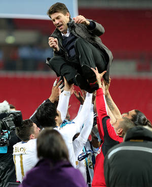 photo - Swansea City's manager Michael Laudrup of Denmark is lifted up by his players after they won the English League Cup following the final soccer match against Bradford City, at Wembley Stadium in London, Sunday, Feb. 24, 2013. Swansea denied Bradford the perfect end to its fairytale run in the League Cup by thrashing the fourth-tier club 5-0 in the final, capping its centenary season with a first major trophy. (AP Photo/PA, Nick Potts) UNITED KINGDOM OUT, NO SALES, NO ARCHIVE
