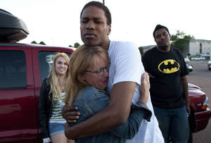 """Photo -   Judy Goos, center left, hugs her daughter's friend, Isaiah Bow, 20, while eyewitnesses Emma Goos, 19, left, and Terrell Wallin, 20, right, gather outside Gateway High School where witnesses were brought for questioning Friday, July 20, 2012, in Aurora, Colo. A gunman wearing a gas mask set off an unknown gas and fired into a crowded movie theater at a midnight opening of the Batman movie """"The Dark Knight Rises,"""" killing at least 12 people and injuring at least 50 others, authorities said. (AP Photo/Barry Gutierrez)"""