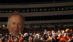 photo - A Cowboy fan carries a large cutout of Boone Pickens in the stands during the Bedlam college football game between the University of Oklahoma Sooners (OU) and the Oklahoma State University Cowboys (OSU) at Boone Pickens Stadium in Stillwater, Okla., Saturday, Nov. 27, 2010. Photo by Chris Landsberger, The Oklahoman ORG XMIT: KOD