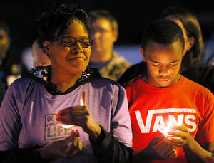 photo - Teri Tharp, left, and Terrance Johnson hold candles during a candlelight vigil for Kittrick Johnson Jr., who died after being in a motorcycle accident on the way to school, in Midwest City, Okla., Wednesday, Nov. 7, 2012. Tharp is Kittrick Johnson's aunt, and Terrance Johnson is a lifelong friend. Kittrick Johnson's family is donating his organs to be transplanted and used the vigil to raise awareness of organ donation as well as remembering Johnson. Photo by Nate Billings, The Oklahoman