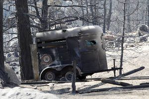 Photo -   The ruins of a horse trailer destroyed by a wildfire is pictured near Conifer, Colo., on Wednesday, March 28, 2012. Two people died in the wildfire that started Monday afternoon. (AP Photo/Ed Andrieski)