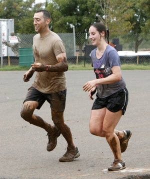 photo - David Leibovich and Anna Christensen run toward the finish line in the Juggernaut mud run at Edmond's J.L. Mitch Park. This was the debut for the Juggernaut in Oklahoma. PHOTO BY PAUL HELLSTERN, THE OKLAHOMAN <strong>PAUL HELLSTERN</strong>