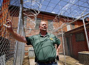Photo - Greer County Sheriff Devin Huckaby talks about his jail while standing in a highly secure outdoor exercise area for his inmates  in  Mangum, Ok on Monday, April 22, 2013.    Photo  by Jim Beckel, The Oklahoman.