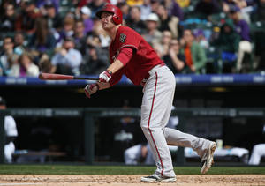 Photo - Arizona Diamondbacks' Mark Trumbo follows the flight of his two-run home run against the Colorado Rockies in the fifth inning of an MLB National League baseball game in Denver on Sunday, April 6, 2014. (AP Photo/David Zalubowski)