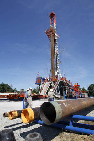 Photo - In this file photo, Range Resources workers stand near a rig that drills into the shale at a well site in Washington, Pa. (AP Photo/Keith Srakocic, File) ORG XMIT: FX110 <strong>Keith Srakocic - AP</strong>