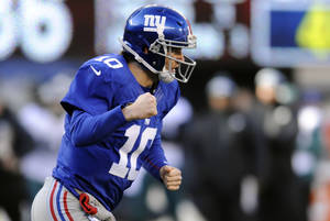 Photo - New York Giants quarterback Eli Manning (10) reacts after throwing a toucdown pass to Rueben Randle during the first half of an NFL football game against the Philadelphia Eagles, Sunday, Dec. 30, 2012, in East Rutherford, N.J. (AP Photo/Bill Kostroun)
