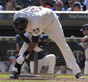 Photo - Minnesota Twins' Aaron Hicks throws his bat between his legs and unbuckles his shin guard after striking out against  Oakland Athletics pitcher Jesse Chavez during the seventh inning of a baseball game on Wednesday, April 9, 2014, in Minneapolis. Oakland won 7-4. (AP Photo/Tom Olmscheid)