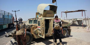 Photo - FILE - In this file photo taken Thursday, June 19, 2014, al-Qaeda-inspired militants stand with captured Iraqi Army Humvee at a checkpoint outside Beiji refinery, some 250 kilometers (155 miles) north of Baghdad, Iraq. The insurgents came at midday, walking across a canal, advancing under cover of mortar fire toward the cluster of three Iraqi villages. Within eight hours, Shiite residents who fled say, they had expelled thousands of them from villages in Salahuddin, a central, majority-Sunni province which links the west to the capital. The insurgents, led by the al-Qaida-inspired Islamic State of Iraq and the Levant, were helped by local Sunnis. The expulsions show how IraqÂ's sectarian mosaic is unraveling in particularly hateful ways, unseen since the mid-2000s when sectarian killings nearly plunged the country into civil war. (AP Photo, File)