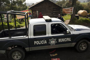 Photo - A municipal police truck arrives to the entrance of Rancho la Mesa, which leads to Rancho La Negra in Tlalmanalco, Mexico, Thursday, Aug. 22, 2013. Mexican authorities said Thursday that they have found a mass grave east of Mexico City and are testing to determine if it holds some of the 12 people who vanished from a bar in an upscale area of the capital nearly three months ago. (AP Photo/Ivan Pierre Aguirre)
