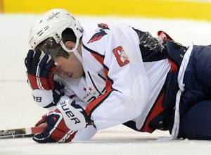 Photo - Washington Capitals' Alex Ovechkin holds his head as he lies on the ice after taking a hit while playing the Winnipeg Jets during preseason NHL hockey game in Belleville, Ontario, on Saturday, Sept. 14, 2013. (AP Photo/The Canadian Press, Sean Kilpatrick)