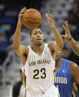 Photo - New Orleans Pelicans forward Anthony Davis (23) grabs a loose ball in the second half of an NBA basketball game against the Orlando Magic in New Orleans, Sunday, Jan. 26, 2014. The Pelicans defeated the Magic 100-92. (AP Photo/Bill Haber).