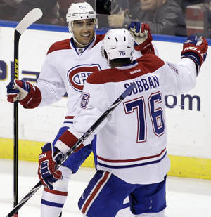 Photo - Montreal Canadiens' Francis Bouillon, left, celebrate with teammate P.K. Subban (76) after scoring a goal against the Florida Panthers during the second period of an NHL hockey game on Sunday, March 10, 2013, in Sunrise, Fla. (AP Photo/Luis M. Alvarez)