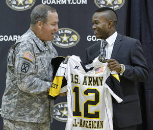 Photo - HIGH SCHOOL FOOTBALL / LT. GEN. BENJAMIN FREAKLEY: Lt. Gen. Benjamin C. Freakley presents an Army All-American jersey to Barry Sanders  during a ceremony at Heritage Hall High School  in Oklahoma City , Monday, October 4, 2011. Photo by Steve Gooch  ORG XMIT: KOD