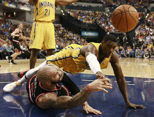 Photo - CORRECTS SPELLING OF BOOZER - Chicago Bulls forward Carlos Boozer, left, passes the basketball as Indiana Pacers center Ian Mahinmi dives for it in the first half of an NBA basketball game in Indianapolis, Friday, March 21, 2014. (AP Photo/R Brent Smith)