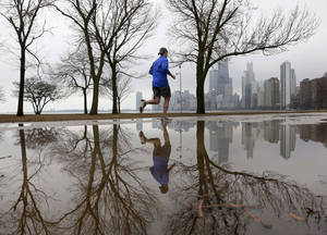 Photo - A lone jogger makes his way along Lake Michigan in unseasonably warm temperatures at Chicago's North Ave. Beach Tuesday, Jan. 29, 2013, in Chicago. Unseasonably warm temperatures broke records in the Chicago area with thunderstorm expected to usher in freezing temperatures and snow Wednesday. (AP Photo/Charles Rex Arbogast)