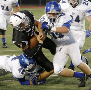 Photo - Putnam City's Braden Hudson is brought down by Sapulpa's Tanner Gregory (42) and Jacob Shanahan (13) during their high school football game at Putnam City in Oklahoma City, Thursday, Sept. 26, 2013. Photo by Bryan Terry, The Oklahoman