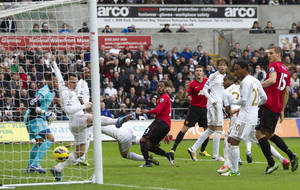 Photo - Manchester United's Patrice Evra, center, scores against Swansea during their English Premier League soccer match at the Liberty Stadium, Swansea, Wales, Sunday Dec. 23, 2012. (AP Photo/Jon Super)